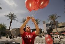 Student setting up red balloons